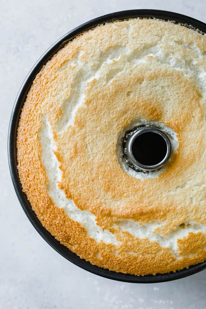 Angel Food Cake that has been lightly browned, still in a tube pan.