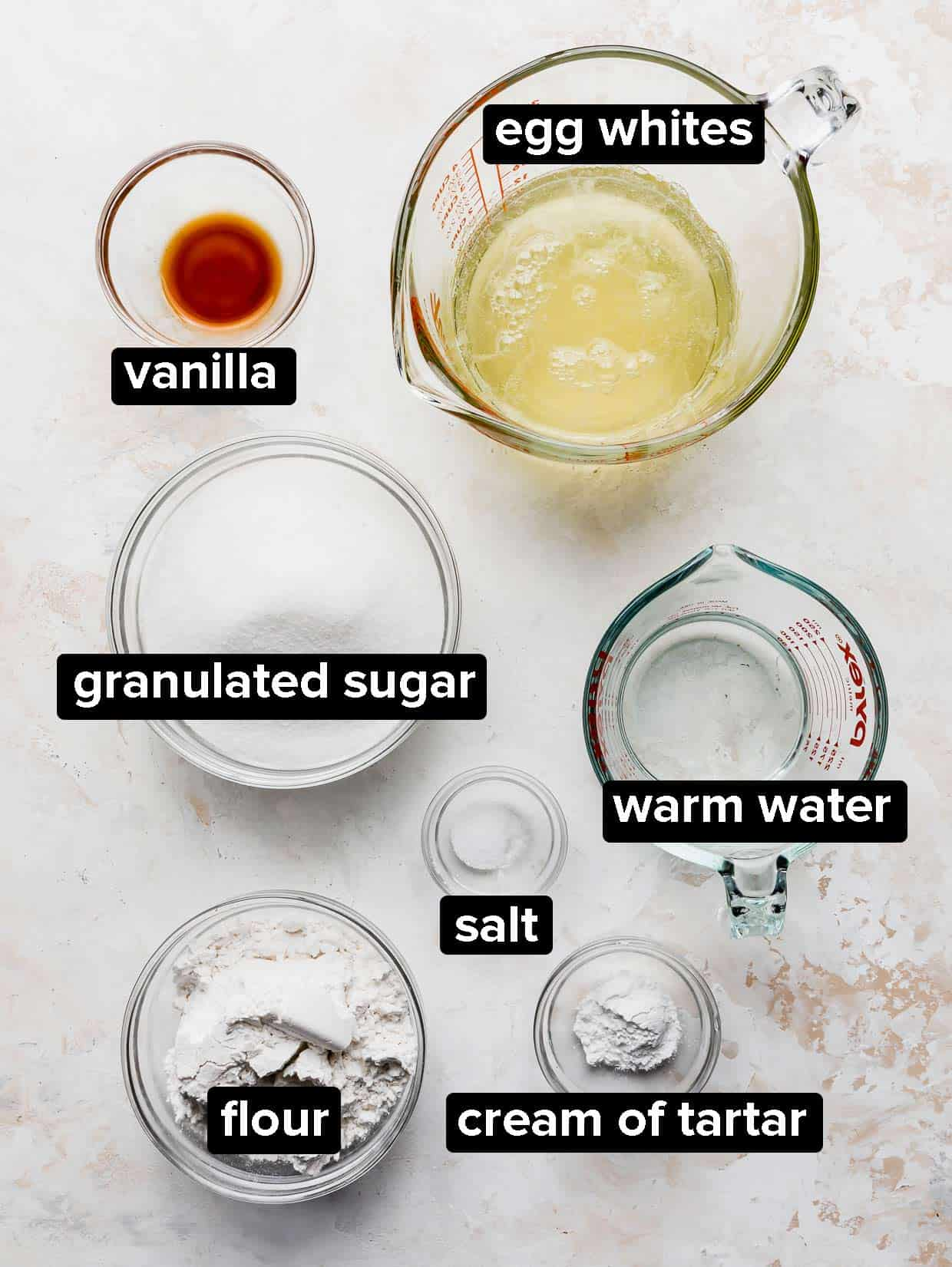 Ingredients used to make angel food cake on a textured cream background.