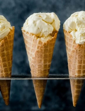 Homemade Creamy Vanilla Ice Cream scooped into three waffle cones.