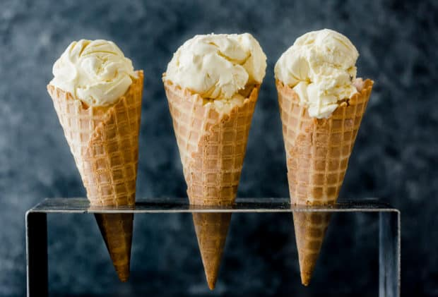 Homemade Creamy Vanilla Ice Cream recipe scooped into three upright waffle cones that are placed in a cone holder.