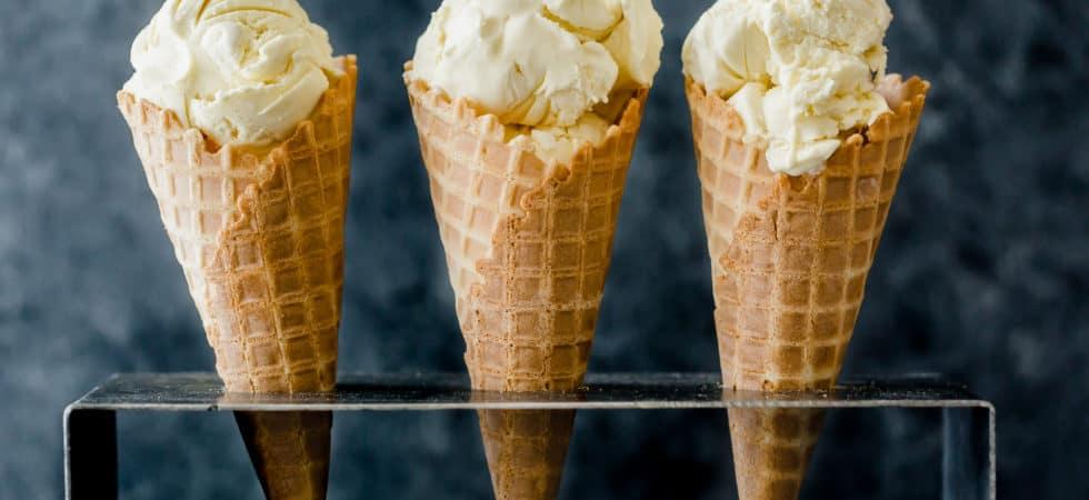Homemade Creamy Vanilla Ice Cream scooped into three waffle cones.
