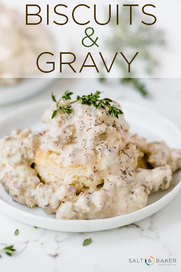 A buttermilk biscuit with homemade gravy and a sprig of thyme on top.