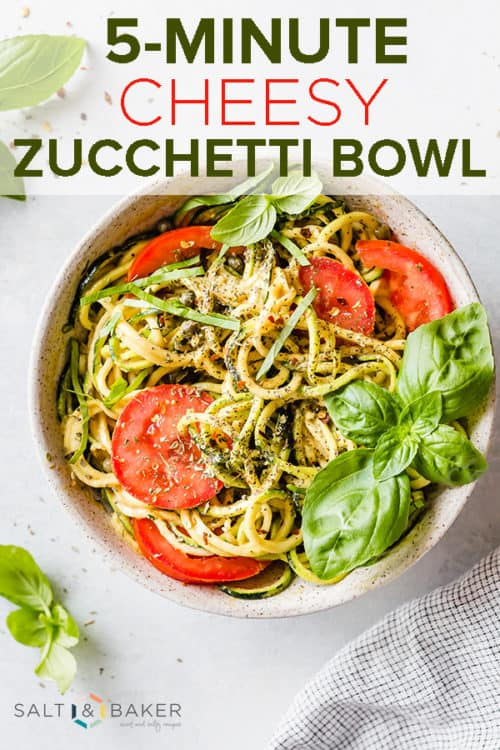 A bowl with zucchini noodles, sliced tomatoes, and fresh basil leaves.