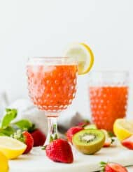 A pitcher pouring strawberry kiwi lemonade into a tall clear glass.