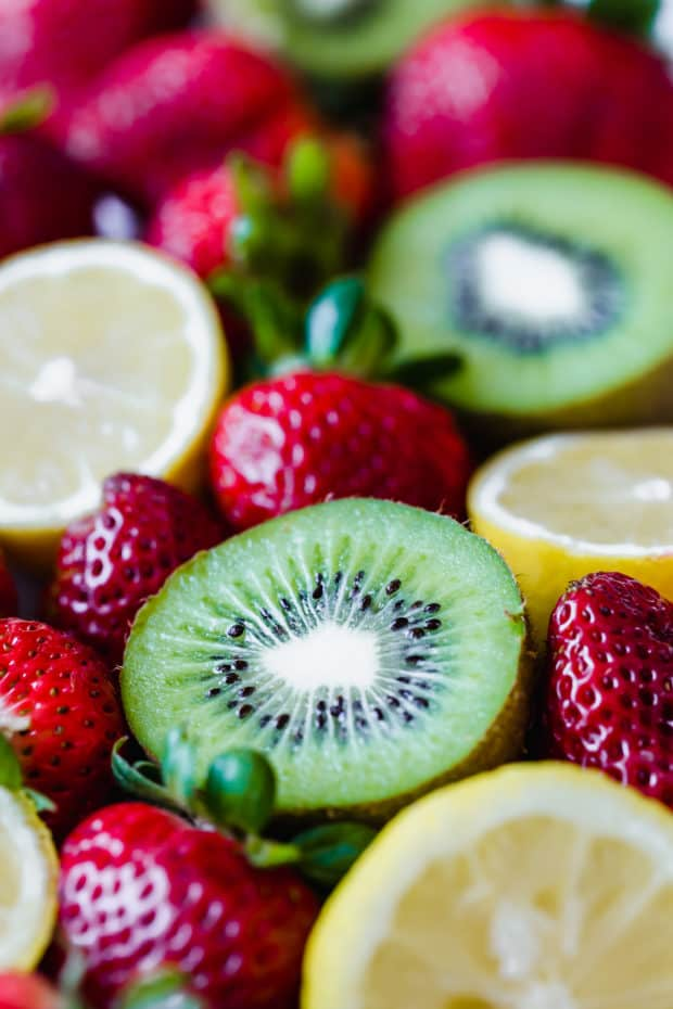 A close up picture of ripe red strawberries and halved lemons and kiwis.