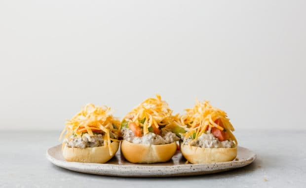 Three hoagie buns on a plate, each topped with beef stroganoff, diced bell peppers, tomatoes, and shredded cheese.