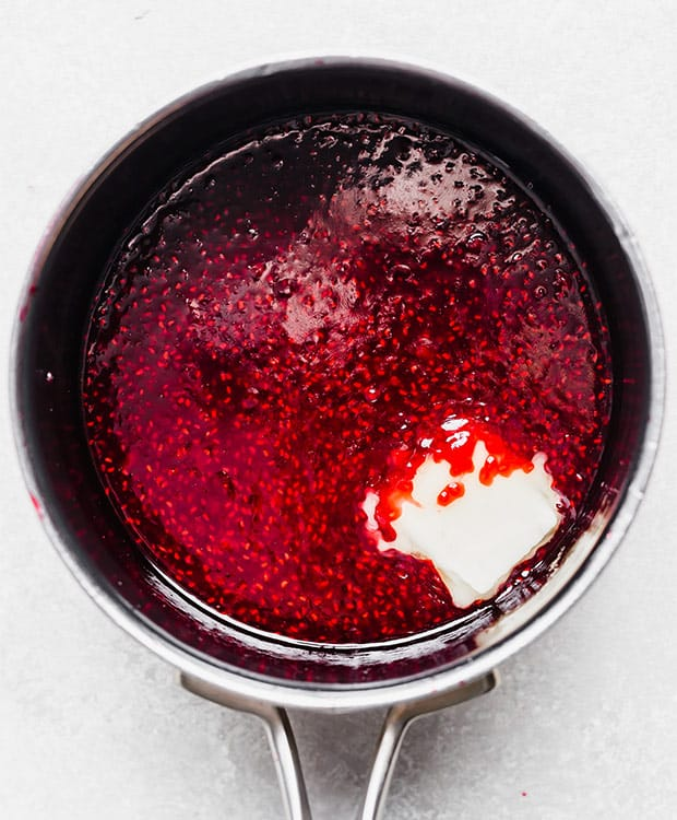 Raspberry sauce and a slice of butter in a small pot.