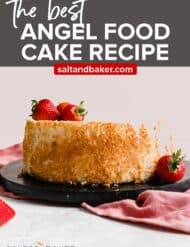 An angel food cake with fresh strawberries on one side of the cake.