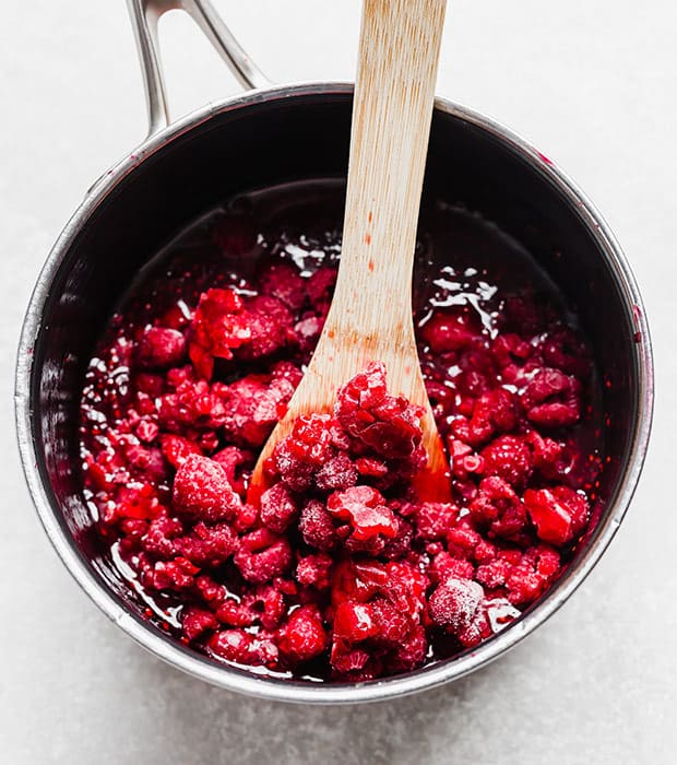 Raspberry sauce in a saucepan with a wooden spoon scooping some up.