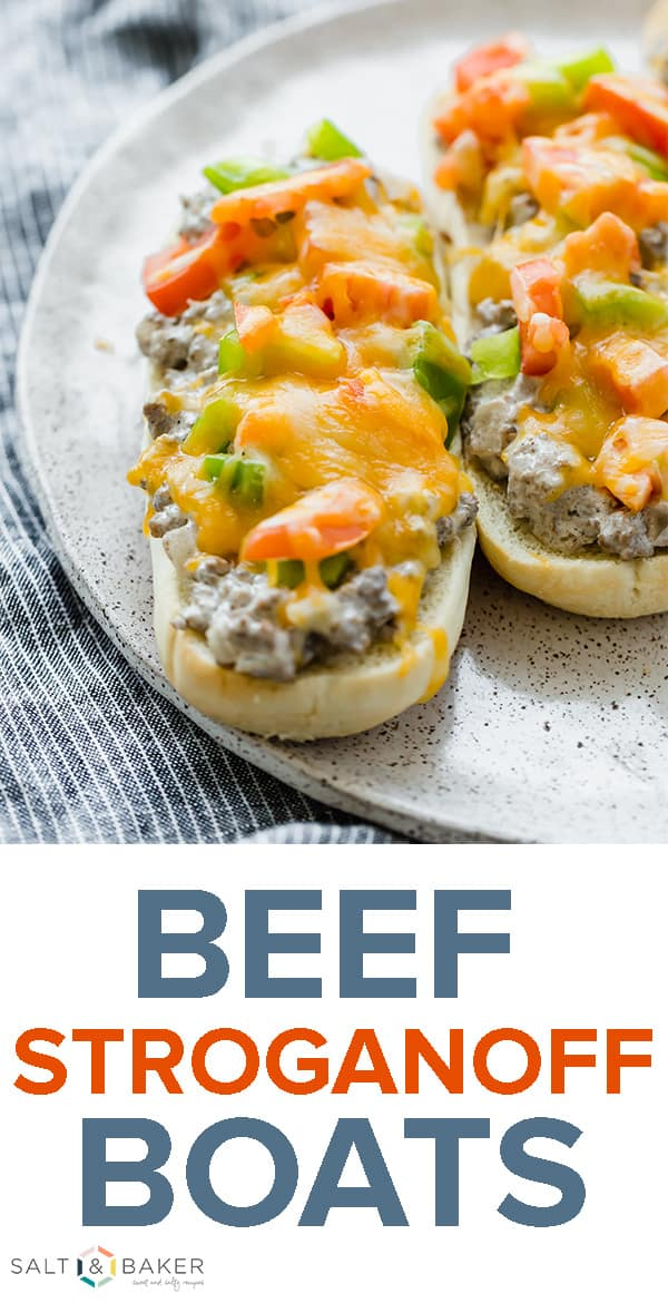 Two hoagie buns topped with beef stroganoff, diced green peppers, tomatoes, and cheese.