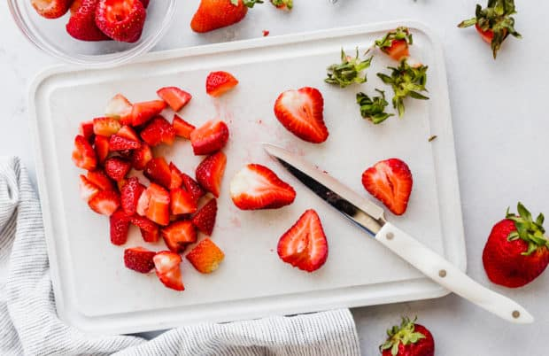 A cutting board with chopped strawberries and a white knife