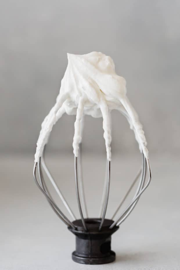 A Kitchen Aid whisk standing on its base with freshly whipped cream on the tip.