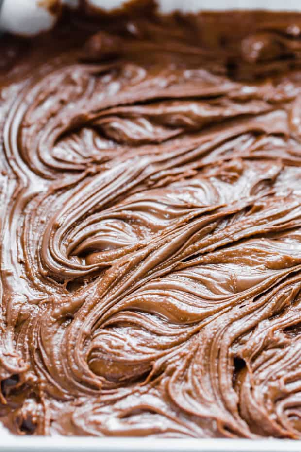 Nutella Brownies batter having dollops of Nutella swirled into the batter.
