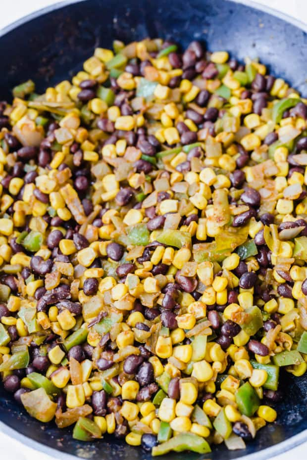 Close up of black beans, corn, green bell pepper, and onion in a saute pan.