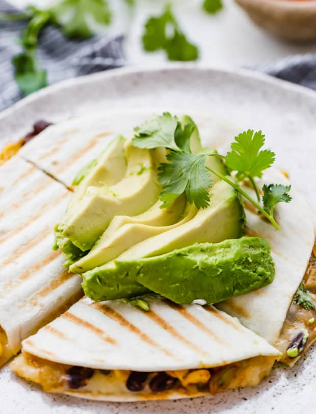 A grilled six inch quesadilla stuffed with a spicy black bean and corn mixture, topped with sliced avocado.