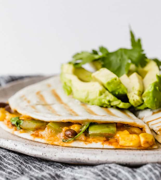 Side photo of a grilled quesadilla stuffed with black beans, corn, peppers, cilantro, and cheese, topped with sliced avocado.