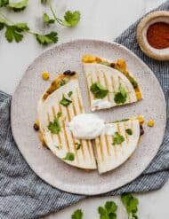 Top view of a 6 inch grilled quesadilla topped with chopped cilantro and a dollop of sour cream.