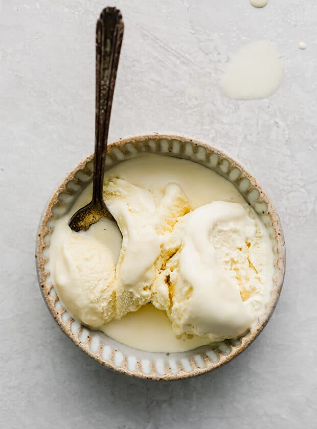 A bowl of homemade vanilla ice cream and a spoon.