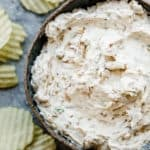 Onion dip in a bowl with ruffled potato chips around the bowl.