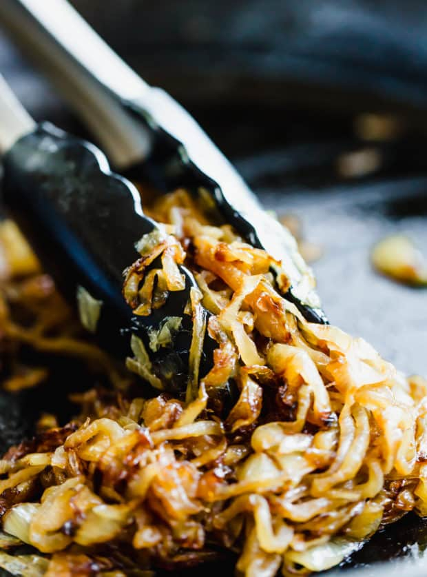 Fully caramelized onions with tongs grasping some of the onions.