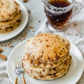 A stack of cinnamon chip pancakes on a plate with maple syrup in a clear glass in the background.
