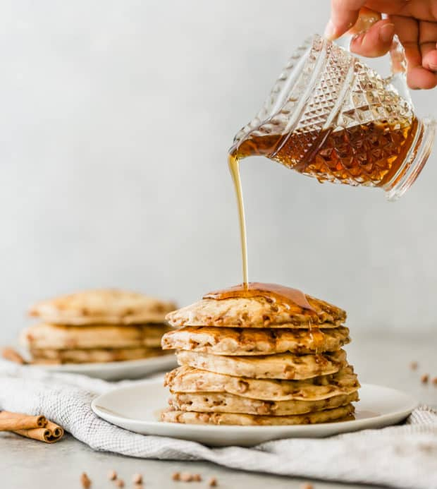 A stack of cinnamon chip pancakes and maple syrup being drizzled overtop.