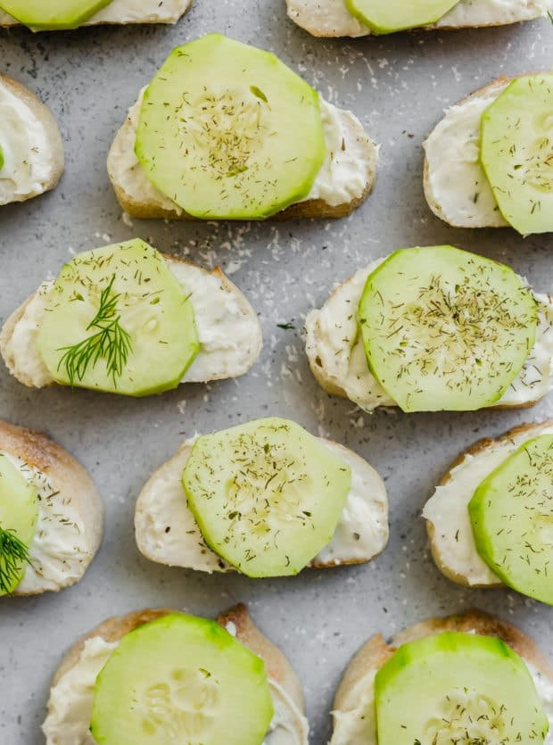 A collection of sliced cucumbers atop a cream cheese mixture on a sliced baguette.
