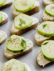 Sliced baguettes layered with a cream cheese spread and sliced cucumber.