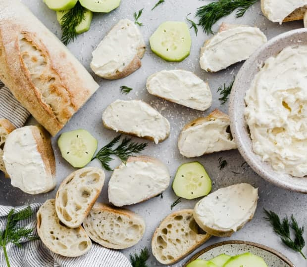 Ranch cream cheese mixture smeared atop sliced baguettes, with cucumbers in the background.