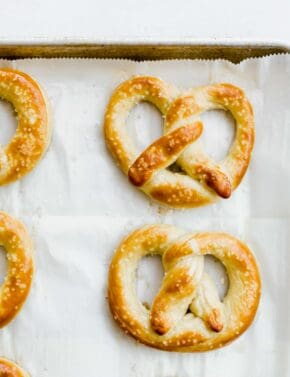 An overhead close up view of a golden brown pretzel on a baking sheet.