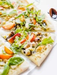 Slice of pizza topped with diced chicken, corn, nectarines, ricotta, and arugula.