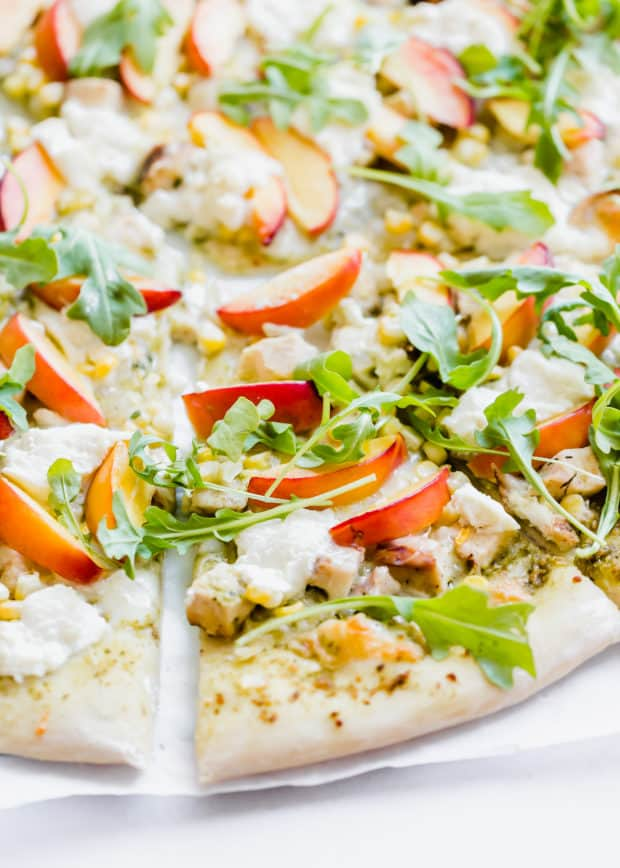 Slice of pizza topped with ricotta, arugula, and nectarines.