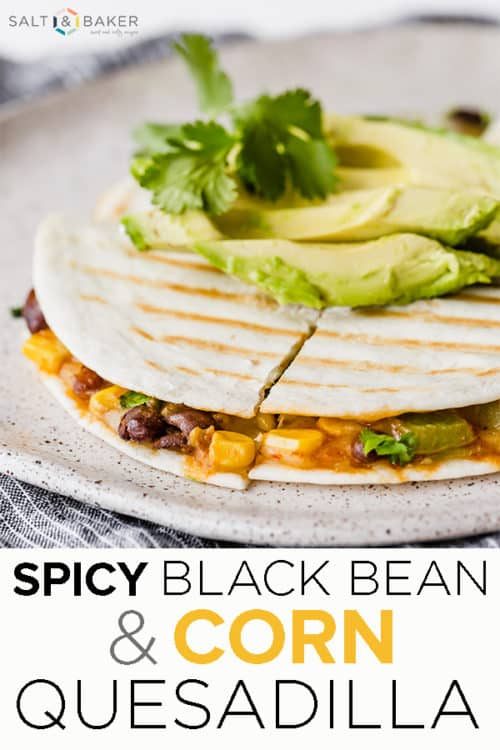 Side angle of a grilled quesadilla stuffed with black beans and corn mixture, topped with a sliced avocado.