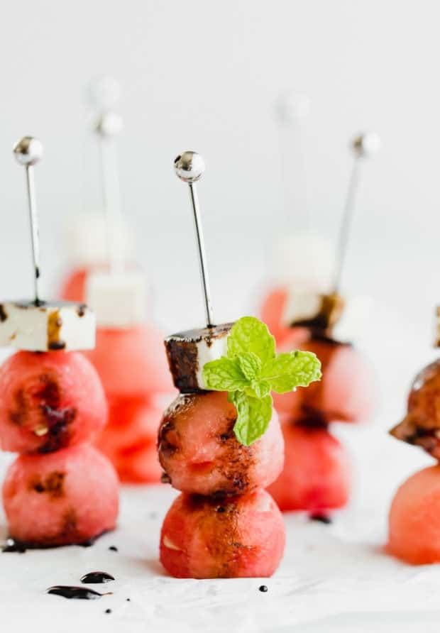 Two watermelon balls and a block of feta on small skewers, drizzled with balsamic reduction and a mint leaf for garnish.