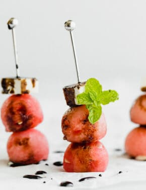 Watermelon balls with a cube of feta cheese on top.