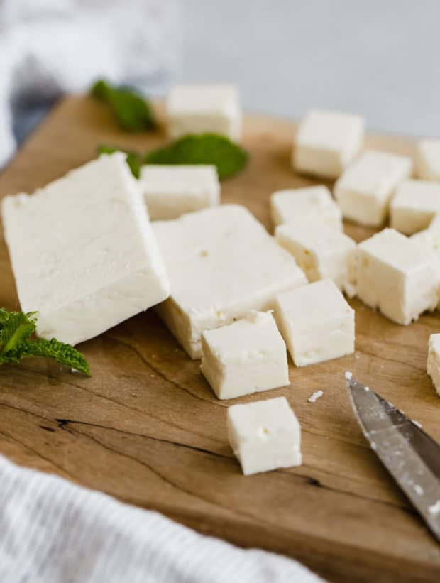 Close up photo of feta cheese on a wooden cutting board cut into small squares.