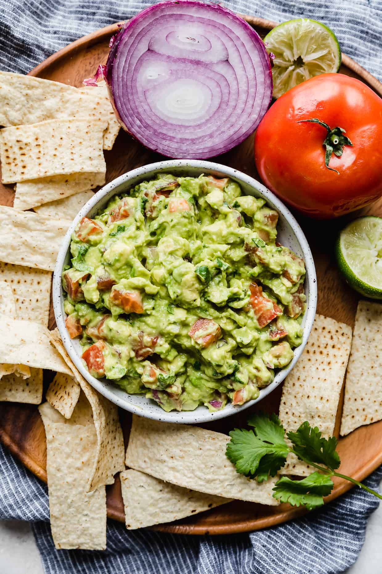 A bowl of the best guacamole on a wooden tray with tortilla chips surrounding it.