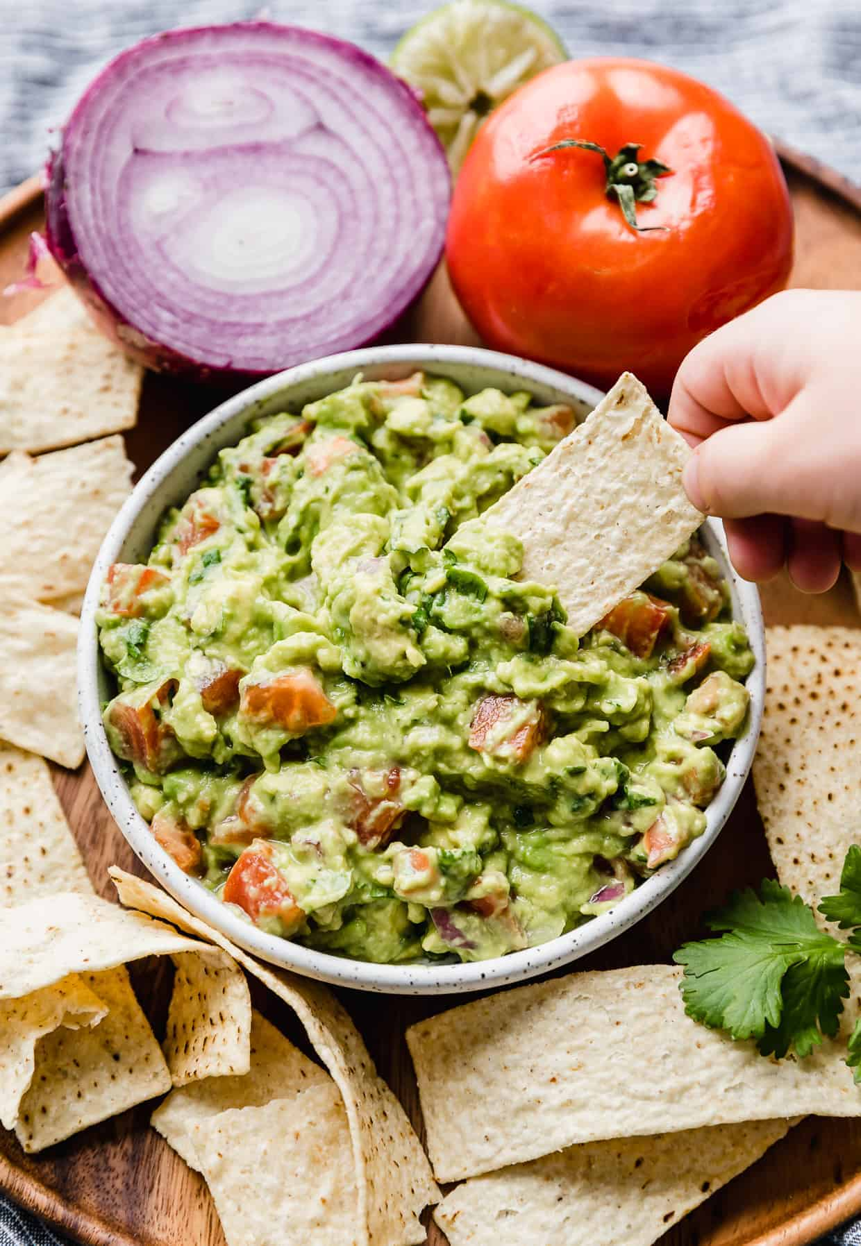 A small hand dipping a tortilla chip into a bowl of fresh guacamole with diced tomatoes in it.