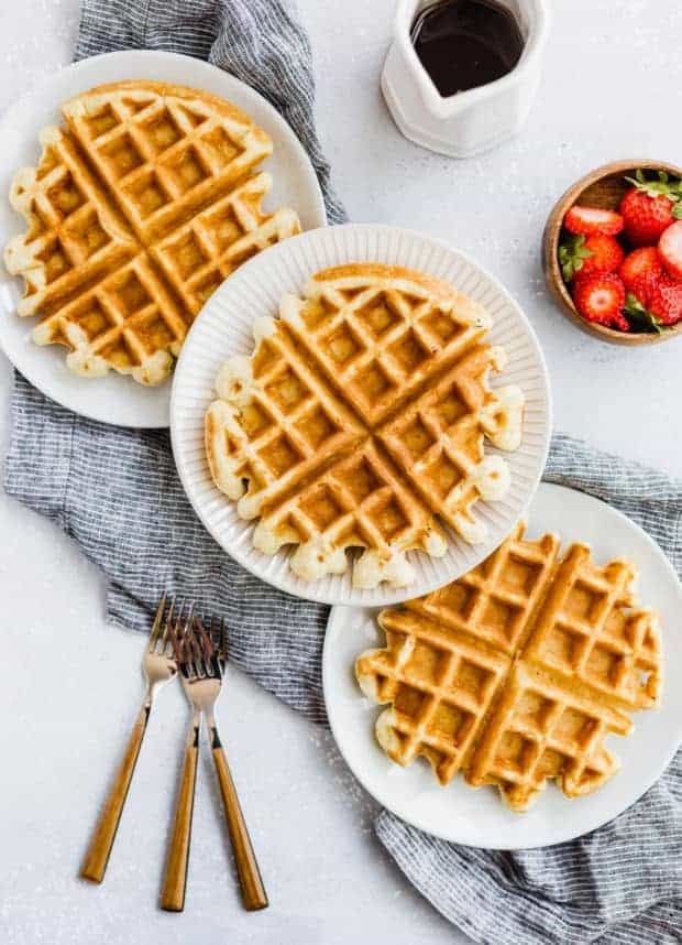 Three buttermilk waffles with three forks to the side.