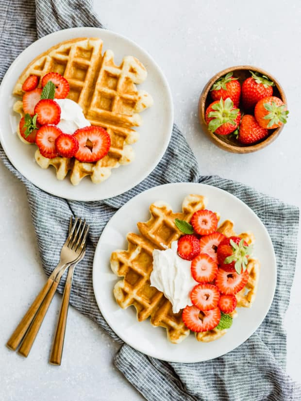 Overhead view of two buttermilk waffles topped with cream and strawberries.