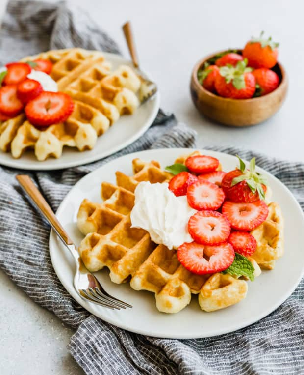 A buttermilk waffle with whipped cream and chopped strawberries on top.