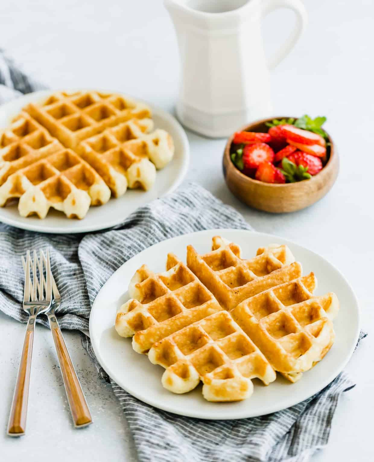 Buttermilk waffle on a plate with a bowl of strawberries in the background.
