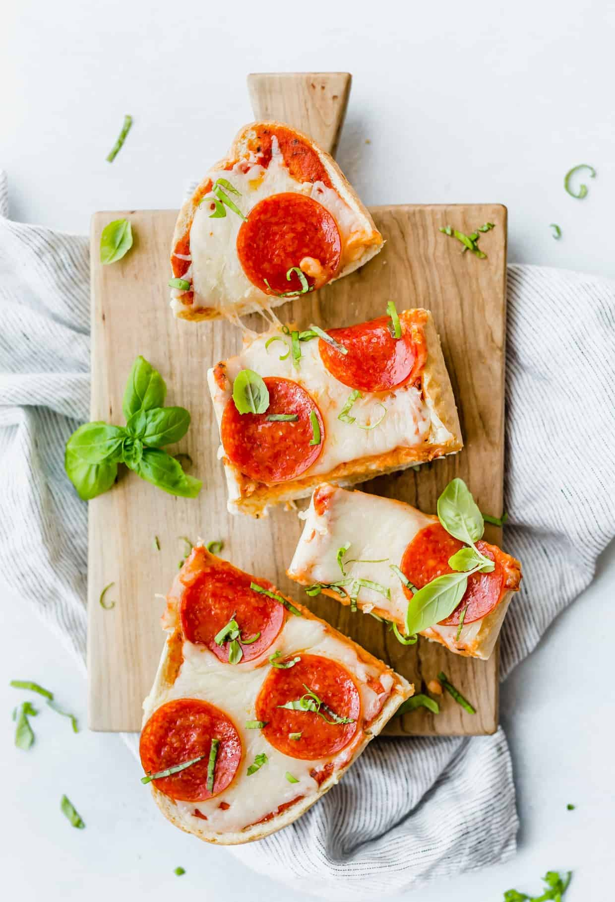 Overhead view of French Bread Pizza with pepperoni on top and a basil garnish.