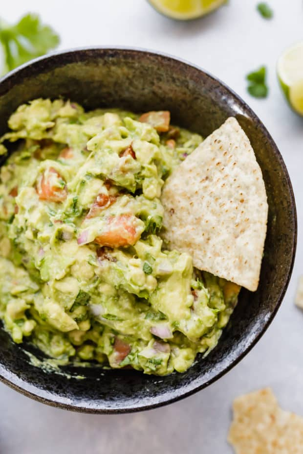 Tortilla chip inserted into a bowl of guacamole.