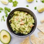 Bowl of guacamole surrounded by tortilla chips, cilantro, and limes.
