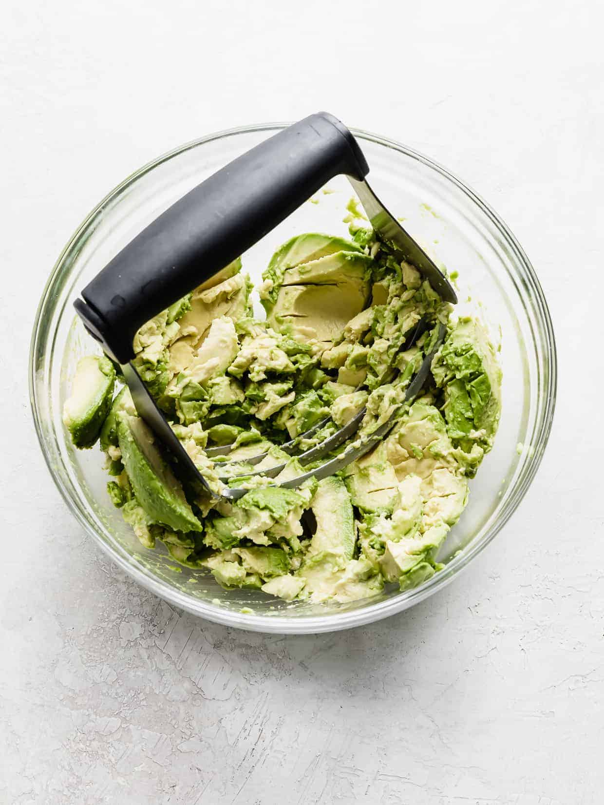 Fresh avocados in a glass bowl with a pastry blender smashing them.