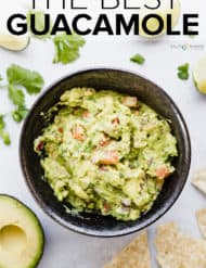 Bowl of guacamole surrounded by tortilla chips, cilantro, and lime wedges.