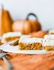 Pumpkin bars with cream cheese frosting with a pumpkin in the background.