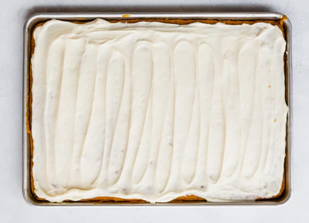 An overhead shot of a baking sheet with pumpkin bars fully cooked, topped with a cream cheese frosting.