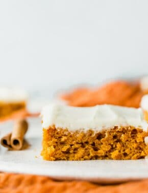 A close up of pumpkin bars on a white plate, topped with cream cheese frosting.